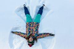 Sikt för hög vinkel av den lyckliga flickan som ligger på snö och flyttar hennes armar och ben uppåt- och neråt att skapa ett snö arkivfoton