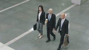 Sikt för hög vinkel av den multietniska företags ledaren som ankommer på modern kontorsbyggnad lager videofilmer