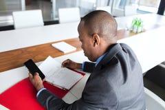 Sikt för hög vinkel av den unga affärsmannen med mappen genom att använda mobiltelefonen på konferenstabellen fotografering för bildbyråer