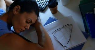 Sikt för hög vinkel av den unga Caucasian kvinnliga ledaren som sover på skrivbordet i ett modernt kontor 4k stock video