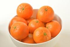 Sikt för hög vinkel av den vita bunken som fylls med orange mandariner, på vit bakgrund arkivbilder