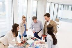 Sikt för hög vinkel av designprofessionell som har diskussion på tabellen i nytt kontor royaltyfri foto