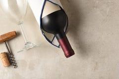 Sikt för hög vinkel av en Cabernet - den sauvignon vinflaskan slogg in i en handduk med vinglaset och korkskruvet royaltyfria bilder