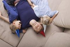 Sikt för hög vinkel av fadern och barn med den konstgjorda mustasch- och partihatten som sover på soffasäng royaltyfri bild