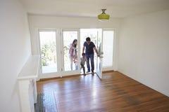 Sikt för hög vinkel av familjen som undersöker det nya hemmet på rörande dag arkivbild