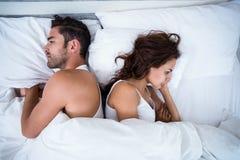 Sikt för hög vinkel av ilskna par på säng arkivfoto