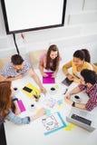 Sikt för hög vinkel av kollegor som diskuterar i möte på det idérika kontoret royaltyfri bild