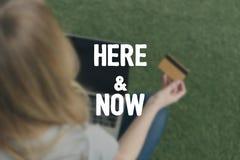 sikt för hög vinkel av kvinnadanandee-shopping med bärbara datorn, medan sitta på gräs, här och nu inskrift Royaltyfria Bilder