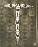 Sikt för hög vinkel av kvinnor som bildar bokstaven T arkivbild