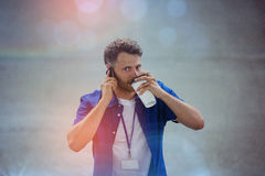 Sikt för hög vinkel av mannen som dricker kaffe, medan tala på mobiltelefonen Arkivfoton