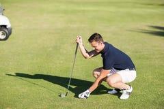 Sikt för hög vinkel av mannen som förlägger golfboll på utslagsplats arkivfoton