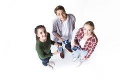Sikt för hög vinkel av tonårs- vänner som rymmer smartphones med facebooklogo Royaltyfria Bilder