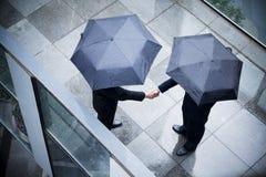 Sikt för hög vinkel av två affärsmän som rymmer paraplyer och skakar händer i regnet Royaltyfria Bilder