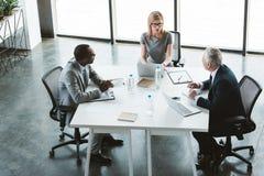 sikt för hög vinkel av yrkesmässigt multietniskt affärsfolk som har konversation under arkivbild