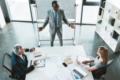 sikt för hög vinkel av yrkesmässigt multietniskt affärsfolk som har konversation under affär royaltyfri bild