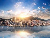 Sikt för Hong Kong stadshorisont från hamn med skyskrapor och solen Royaltyfri Bild