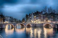 Sikt för Keizersgracht inersectionbro av den Amsterdam kanalen och historiska hus under skymningtid, Netherland arkivbilder