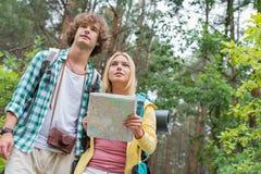 Sikt för låg vinkel av att fotvandra par med översikten i skog Royaltyfri Fotografi