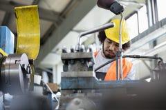 Sikt för låg vinkel av den unga manuella arbetaren som arbetar på maskineri i metallbransch Royaltyfri Bild