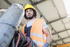 Sikt för låg vinkel av den unga rörande gascylindern för manuell arbetare i metallbransch Arkivfoton