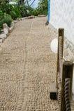 Sikt för låg vinkel av den vita väggen för medelhavs- kiselstenkullerstenbana Royaltyfri Fotografi