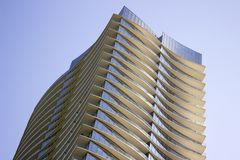 Sikt för låg vinkel av en modern företags byggnad med gulaktiga överhäng i varje golv royaltyfri fotografi