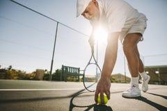 Sikt för låg vinkel av en tennisspelare som framåtriktat böjer för att välja lodisarna royaltyfri fotografi