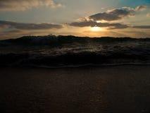 Sikt för låg vinkel av en våg som plaskar på kust under en molnig himmel på solnedgången royaltyfri bild
