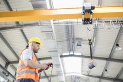 Sikt för låg vinkel av för fungeringskran för manuell arbetare lyftande stål i bransch royaltyfri foto