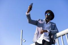 Sikt för låg vinkel av hatten och solglasögon för ung afrikansk svart man som den bärande lutar på ett metalliskt staket som kopp arkivbild