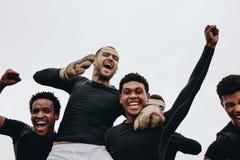 Sikt för låg vinkel av spelare som bär deras lagkamrat på skuldror som firar framgång Grupp av lyckligt fira för fotbollspelare arkivfoton