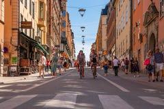 Sikt för låg vinkel av två män som cyklar, och att gå för folk Arkivbilder