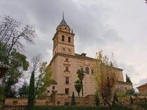 Sikt för låg vinkel på kyrka av Santa Maria de Alhambra, Granada, Spanien som omges av träd på en molnig dag arkivbild