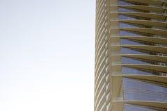 Sikt för låg vinkel för sida av en modern företags kontorsbyggnad med gulaktiga överhäng i varje golv royaltyfri fotografi