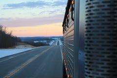 Sikt för lastbilsförare` s av ett kallt som är spegelförsedd, soluppgång arkivfoton
