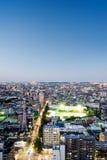 Sikt för natt för panorama- modernt öga för stadshorisontfågel flyg- under dramatiskt neonglöd och härligt mörker - blå himmel i  Royaltyfri Foto