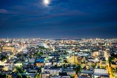 Sikt för natt för panorama- modernt öga för stadshorisontfågel flyg- under dramatiskt neonglöd och härligt mörker - blå himmel i  Arkivbild
