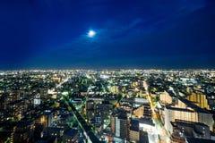 Sikt för natt för panorama- modernt öga för stadshorisontfågel flyg- under dramatiskt neonglöd och härligt mörker - blå himmel i  Arkivfoton