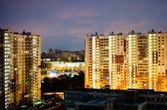 sikt för natt för stadsexponering lång Mång--våning hyreshusar med lysande fönster mot en mörk himmel arkivbilder