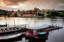 Sikt för Prague slott från den Vltava flodbanken, fartyg framme, under skymningen Arkivfoto
