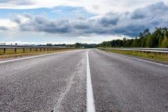 Sikt för punkt för asfaltväg låg i molnig dag Royaltyfria Foton