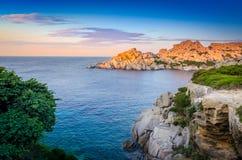 Sikt för solnedgång för stenig kustlinje för hav färgrik, Sardinia Arkivbild