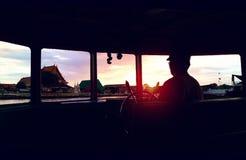 Sikt för solnedgångBangkok flodstrand från silhouetted boat& x27; s-fönster Arkivbilder