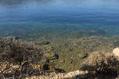 Sikt för sommartid från stranden till den kristallklara Poros för fjärd för förälskelse för havsvatten ön Grekland Arkivfoto