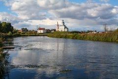 Sikt för Suzdal kyrka- och Kamenka flod 100f 2 8 28 för kameraafton f för 301 ai velvia för sommar för nikon s för fujichrome för Arkivfoton