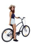 Sikt för tillbaka sida av en kvinna med en cykel royaltyfri foto