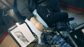 Sikt från över av den manliga prosthetic armen som får tatuerad stock video