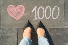 Sikt från över, kvinnlig fot med något liknande för text 1000 i sociala nätverk som är skriftliga på den gråa trottoaren Royaltyfri Foto