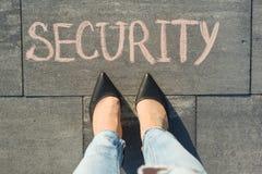Sikt från över, kvinnlig fot med textsäkerhet som är skriftlig på den gråa trottoaren royaltyfri bild