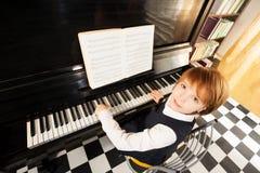 Sikt från överkant av flickan i enhetligt spela piano Royaltyfri Fotografi